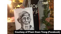 Một thanh niên Hà Nội cầm trên tay tấm hình ông Lê Đình Kình trong buổi lễ ngày 12 tháng Giêng. (Photo courtesy of Facebook user Pham Doan Trang)