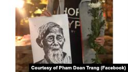 Một thanh niên ở Hà Nội mang hình ông Lê Đình Kình tại buổi lễ tưởng niệm hôm 12 tháng Giêng, 2020. (Photo courtesy of Facebook user Pham Doan Trang)