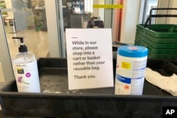 In this Sunday, March 29, 2020, photo, a sign posted at an entrance to a 365 Whole Foods store advises customers not to use their own bags while shopping in Lake Oswego, Ore. (AP Photo/Gillian Flaccus)