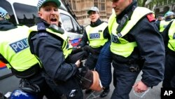 British police officers arrest anti-fascist demonstrators protesting against members of the British National Party [not seen], during a demonstration over the May 22 murder of soldier Lee Rigby by Muslim extremists, in central London, June 1, 2013.