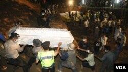 Para relawan dan polisi Indonesia mengangkat peti jenazah korban Merapi dalam pemakaman massal di Seyegan, Sleman hari Minggu 7 November 2010.