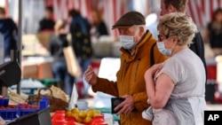 Orang lanjut usia menggunakan masker untuk melindungi dari virus corona tengah berbelanja di pasar di Aachen, Jerman, Kamis, 9 April 2020. (Foto: AP)