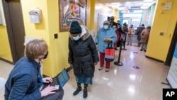 23일 미국 뉴욕주 브루클린의 한 아파트에 마련된 신종 코로나바이러스 백신 임시 접종소에 접종 대상자들이 줄 서 있다.
