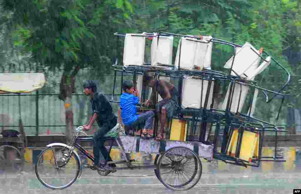 인도 알라하바드에서 한 남성이 인력거에 짐을 가득 실은채 빗속을 운전하고 있다.