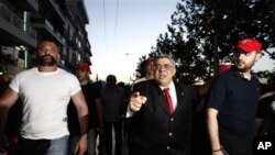 Bersama para pendukungnya, Nikolaos Michaloliakos, Ketua Partai Golden Dawn, berjalan penuh kemenangan melewati jalan-jalan di Athena (photo, 6/5/2012).
