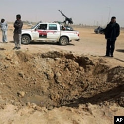 Libyan rebels inspect a crater caused by a bomb dropped by a plane in Ajdabiya on Mar 14 2011 as Libyan strongman Moamer Kadhafi's forces shelled rebel positions