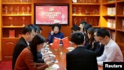 """Cheng Hong (giữa, đằng sau), bí thư đảng ủy Tập đoàn Triều Tinh, tiến hành một buổi học tập tư tưởng Tập Cận Bình với các đảng viên khác sử dụng ứng dụng điện thoại """"Học Tập Cường Quốc"""" trong phòng sinh hoạt ở Bắc Kinh, Trung Quốc, ngày 25 tháng 2, 2019."""
