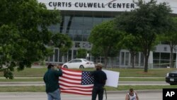 Men hold a sign and a U.S. flag across the street from the Curtis Culwell Center, where two men opened fire at an event soliciting cartoons of the Prophet Muhammad, in Garland, Texas, May 5, 2015.