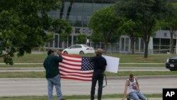 在2015年5月5日两名枪手袭击穆罕默德卡通画比赛的地点,有人手持美国国旗。