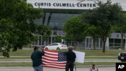 FILE - Men hold a sign and a U.S. flag across the street from the Curtis Culwell Center, where two men opened fire at an event soliciting cartoons of the Prophet Mohammad, in Garland, Texas, May 5, 2015.
