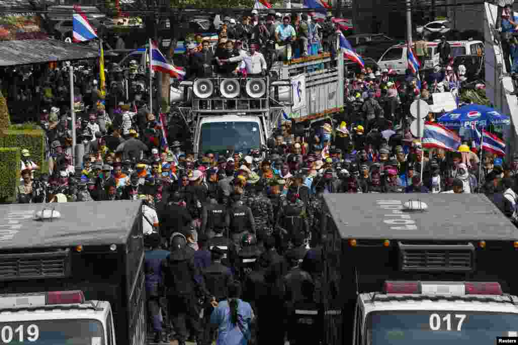 Riot police and soldiers stand guard as anti-government protesters gather at the gates of the Army Club where Prime Minister Yingluck Shinawatra was holding a meeting in Bangkok, Jan. 28, 2014.