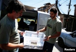 FILE - Technicians carry containers filled with Aedes aegypti mosquitoes with the dengue-blocking Wolbachia bacteria before they are released at the Tubiacanga neighborhood in Rio de Janeiro, Sept. 24, 2014. Similar work has been done in Australia, Vietnam and Indonesia.
