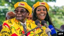 FILE - This file photo taken on November 8, 2017 shows Zimbabwe's President Robert Mugabe (L) addressing party members with Grace Mugabe (R) at his side. (AFP PHOTO / Jekesai NJIKIZANA)