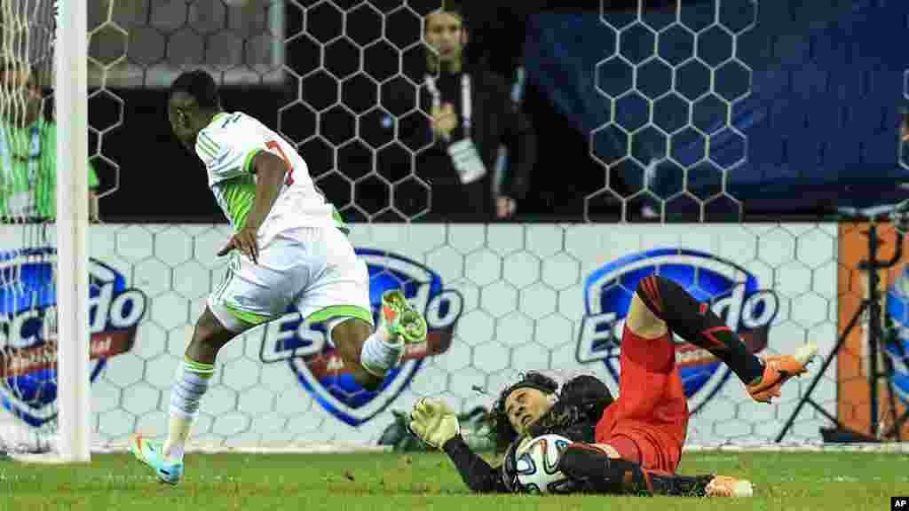 Nigeria midfielder Ahmed Musa (7) makes contact with Mexico goal keeper Guillermo Ochoa (1) during a scoring attempt in the first half of a soccer friendly at the Georgia Dome.