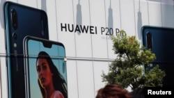 មនុស្សម្នាដើរកាត់ផ្ទាំងពាណិជ្ជកម្មសម្រាប់ក្រុមហ៊ុន Huawei នៅខាងក្រៅហាងលក់គ្រឿងអេឡិចត្រូនិច នៅក្នុងក្រុងតូក្យូ ប្រទេសជប៉ុន កាលពីថ្ងៃទី៦ ខែសីហា ឆ្នាំ២០១៨។