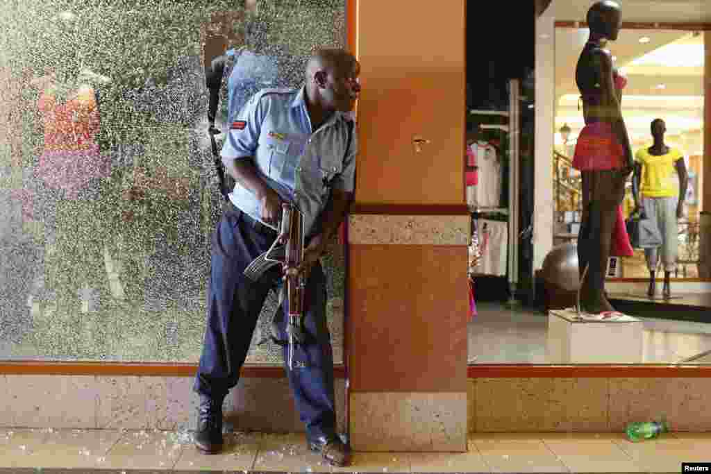 A police officer tries to secure an area inside the Westgate Shopping Center where gunmen went on a shooting spree in Nairobi September 21, 2013.