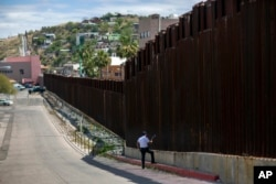 In this April 1, 2017, photo, a man in Nogales, Arizona, talks to his daughter and her mother who are standing on the other side of the border fence in Nogales, Mexico. President Donald Trump has promised his supporters a wall along the entire U.S.-Mexican border.