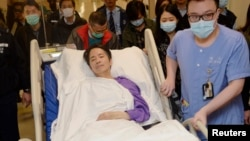 FILE - Ming Pao's former chief editor Kevin Lau, who was brutally attacked, is transferred to a private ward in Eastern Hospital after spending three days in intensive care in Hong Kong, March 1, 2014.
