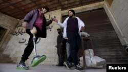 Khamis (R), 24, helps a man with an amputated leg walk using an artificial limb in the rebel-controlled area of Maaret al-Numan town in Idlib province, Syria, March 20, 2016.