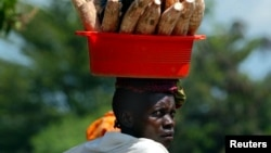 FILE - A Burundian woman carries cassava home from the market in Kinama, a suburb in Burundi's capital, Bujumbura.