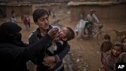 Seorang pekerja medis Pakistan (kiri) memberikan vaksin polio kepada seorang anak di sebuah perkampungan kumuh di Islamabad. (Foto: Dok)
