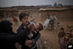 FILE - A Pakistani health worker, left, gives a polio vaccine to a child in a poor neighborhood that hosts people displaced from tribal areas and Afghan refugees, on the outskirts of Islamabad, Pakistan, Jan. 22, 2014.