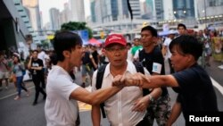 Disputa entre dos manifestantes frente al edificio del gobierno de Hong Kong.