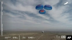 In this image from video made available by Blue Origin, the New Shepard capsule uses parachutes to land during a test in West Texas on Wednesday, April 14, 2021. (Blue Origin via AP)