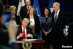 U.S. President Donald Trump signs an executive order at Homeland Security headquarters in Washington, U.S., January 25, 2017
