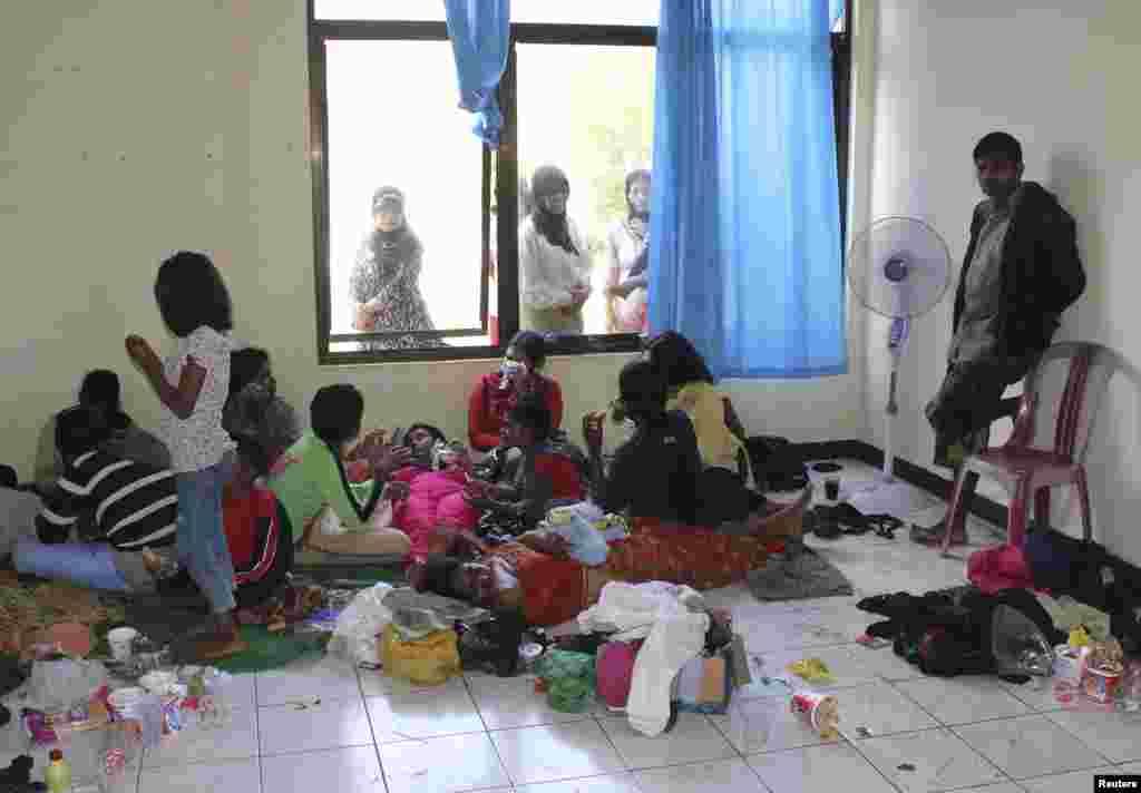 Para terduga pencari suaka yang menumpang kapal yang kemudian terbalik, berada di tempat penampungan sementara dekat Pantai Jayanti, Jawa Barat (24/7).