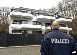 APTOPIX Germany France Plane Crash, A police officer stands in front of a house where the co-pilot of the crashed Germanwings airliner jet is supposed to have lived in an apartment, in Duesseldorf, Germany, Thursday March 26, 2015 during investigations of the crash of an aircraft...
