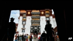 """Chinese tourists pose for a picture while showing """"v"""" signs at the Potala palace in Lhasa"""