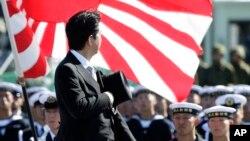 Thủ tướng Nhật Bản Shinzo Abe duyệt hàng quân danh dự của Lực lượng Phòng vệ Nhật Bản (SDF) tại Căn cứ Asaka, phía bắc Tokyo. Kế hoạch nới rộng sứ mạng của Lực lượng Tự vệ Nhật Bản của ông Abe vấp phải sự chống đối của phe chủ hoà trong nước và những sự chỉ trích của các nước láng giềng, đặc biệt là Trung Quốc.