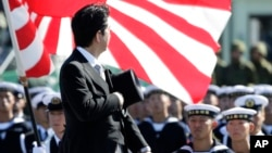 FILE - Japanese Prime Minister Shinzo Abe reviews members of Japan Self-Defense Forces (SDF) during the Self-Defense Forces Day at Asaka Base, north of Tokyo, Sunday, Oct. 27, 2013.