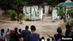 Warga berdiri di depan daerah yang digenangi banjir di Kampung Sewu di Solo, Jawa Tengah (19/6).