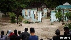 Cư dân đứng trước một khu vực bị ngập lụt ở Kampung Sewuresidential ở Solo, Trung Java, Indonesia, ngày 19/6/2016.