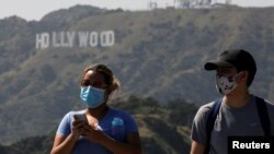 People wearing face masks walk past the Hollywood sign in the distance, after a partial reopening of Los Angeles hiking trails during the outbreak of the coronavirus disease (COVID-19) at Griffith Park in Los Angeles, California, U.S., May 9, 2020. REUTER