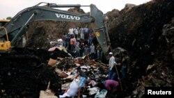 Une excavatrice creuse dans une montagne de déchets en présence de secouristes à la recherche de personnes disparues après l'éboulement de la décharge de Koshe, à Addis Ababa, le 13 mars 2017.