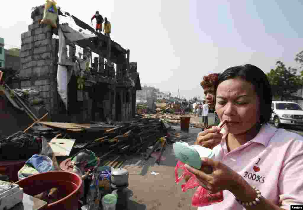 A woman applies lipstick while her family's concrete house is being demolished in a squatter colony in Tondo, Manila.