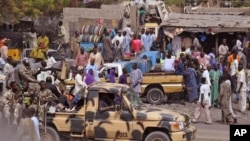 File - Nigerian soldiers ride on the back of an armed truck as they patrol at a local market Tuesday, Jan. 27, 2015, after recent violence in surrounding areas at Maiduguri, Nigeria. Islamic extremists are rampaging through villages in northeast Nigeria's