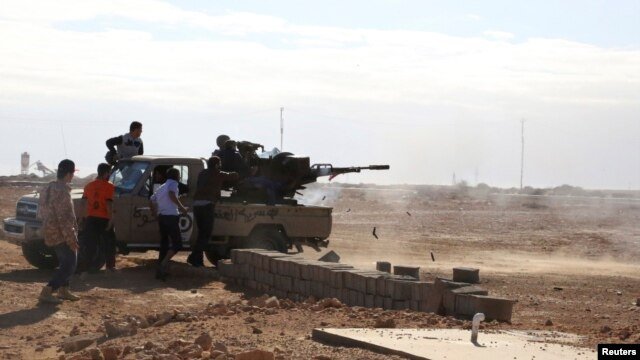 FILE - Fighters are seen firing a vehicle-mounted weapon on the outskirts of Sidra, Libya. The report describes unlawful killings, including executions of people taken captive.