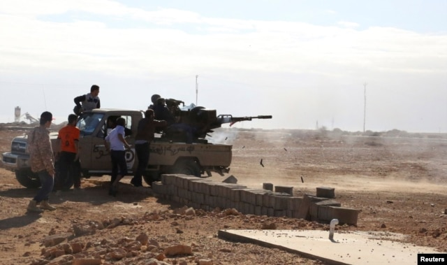 FILE - Fighters are seen firing a vehicle-mounted weapon on the outskirts of Sidra, Libya. Libya's political crisis has persisted since the overthrow of former leader Moammar Gadhafi.