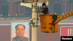 FILE - A man works on a security camera that was installed at Tiananmen Square in Beijing, November 1, 2013. (REUTERS/Kim Kyung-Hoon)