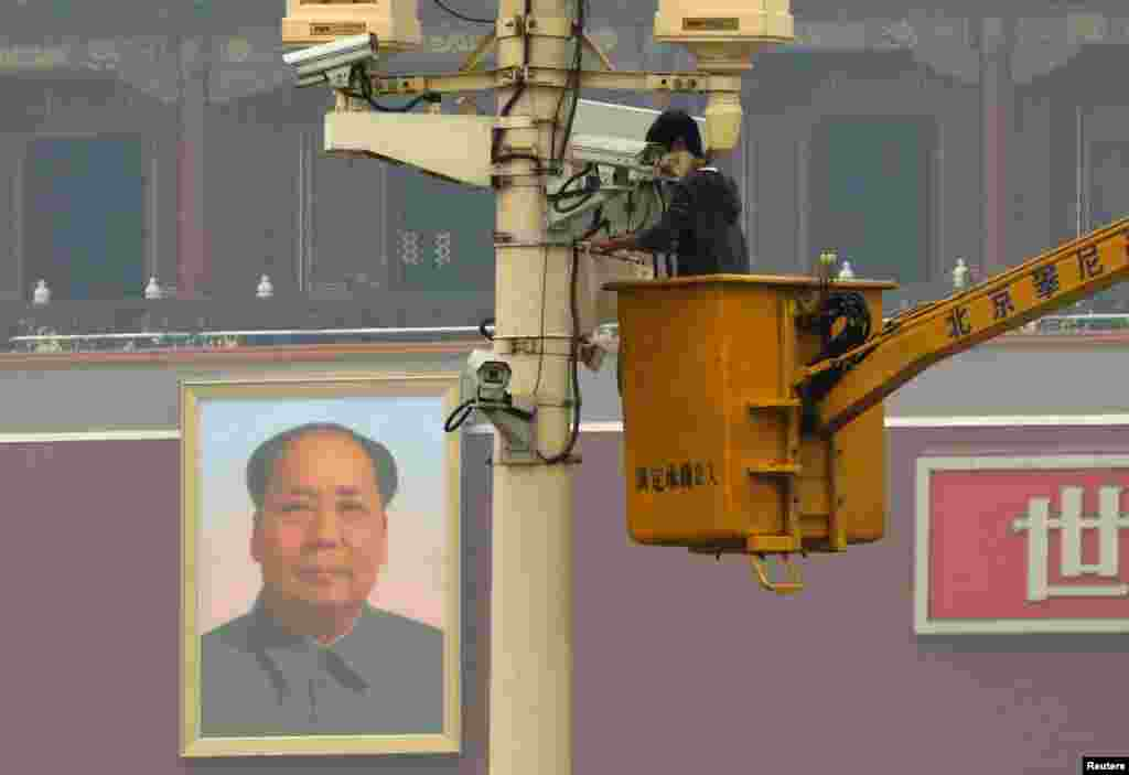 A man installs a security camera  at Tiananmen Square in Beijing, Nov. 1, 2013, very close to the site of a fatal vehicle crash in which five people died.