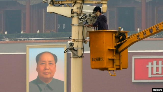 A man works on a security camera that was installed at Tiananmen Square in Beijing, November 1, 2013. China's domestic security chief believes a fatal vehicle crash in Beijing's Tiananmen Square in which five died was planned by a Uighur separatist group,