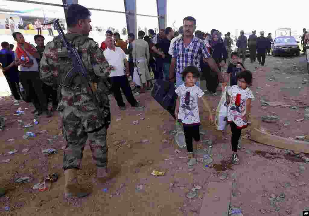 Polisi Kurdi berjaga-jaga sementara para pengungsi dari Mosul mengarah ke wilayah otonom Kurdi di Irbil, Irak, 350 kilometer dari Baghdad (10/6).
