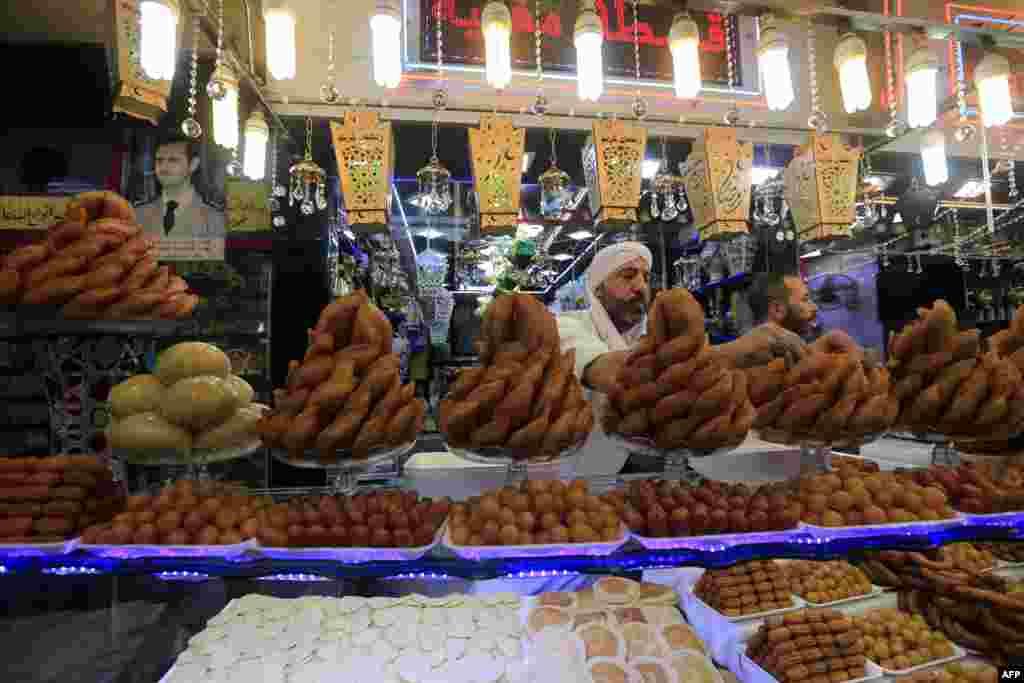 بازار داغ شیرینی فروش ها در ماه رمضان در سوریه. شیرینی فروش در حال چیدن شیرین های افطار است.