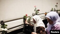 Bosnian women touches one of three trucks carrying 520 coffins of newly identified victims of Srebrenica massacre