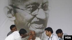 Tim dokter memeriksa aktivis Anna Hazare di depan potret raksasa Mahatma Gandhi, Selasa (23/8).