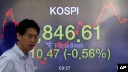 A currency trader walks by a screen showing the Korea Composite Stock Price Index (KOSPI) at the foreign exchange dealing room in Seoul, South Korea, Thursday, April 16, 2020. Asian stocks were mostly lower Thursday after unexpectedly weak U.S…